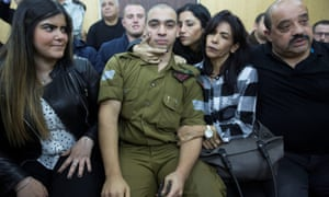 Elor Azaria in court, surrounded by his family.