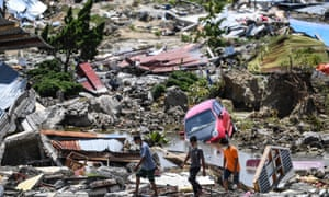 Residents walk through debris in Perumnas Balaroa village in Palu, Indonesia's Central Sulawesi on 2 October 2018.