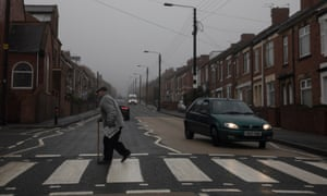 A man with a stick walks across a zebra crossing on a grey day in Stanley, Durham – a county that voted for Brexit.
