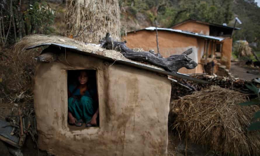 A teenage girl sits in a shed in the hills of Legudsen village in western Nepal's Achham district