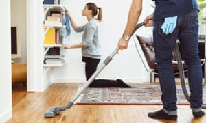 A man vacuums while a woman cleans shelves at home.