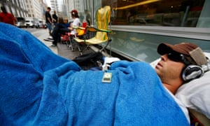A man sleeps near the Apple Store on New York's Fifth Avenue, waiting to buy the latest iPhone.