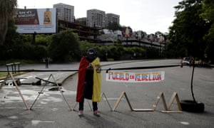 An opposition supporter blocks a road during a strike called in Caracas, Venezuela.