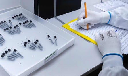 A laboratory technician inspects defective syringes which were set aside by an automatic inspection machine.