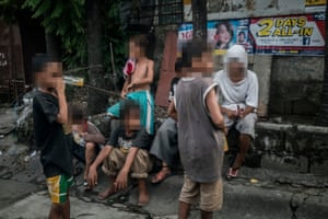 A group of young boys sniff glue on a street corner in Payatas