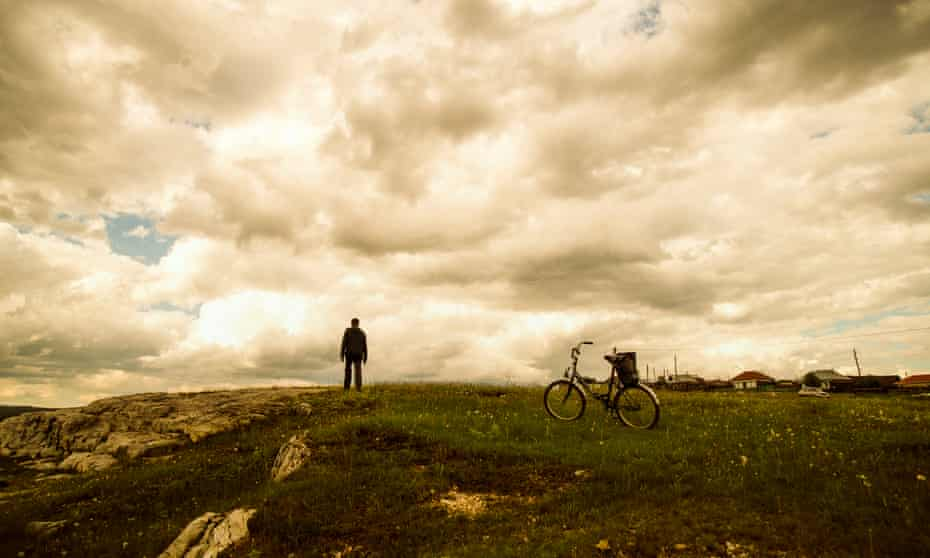 Caucasian man with bicycle in field