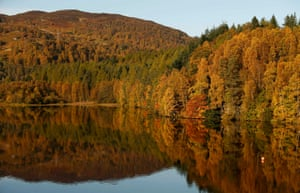 Autumn leaves are reflected in the water of Loch Faskally, in Pitlochry, Scotland
