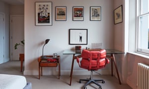 The office with a glass-top desk with wooden legs, swivel chair with red padding, and pictures on the wall above