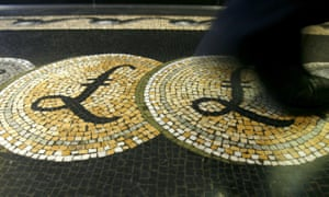 An employee walks over a mosaic depicting pound sterling symbols on the floor of the front hall of the Bank of England in London<br>An employee is seen walking over a mosaic of pound sterling symbols set in the floor of the front hall of the Bank of England