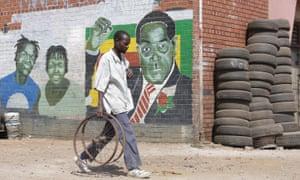 A man walks past a mural depicting Robert Mugabe in Harare, Zimbabwe
