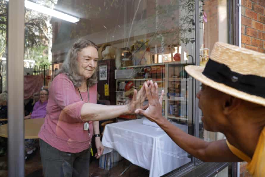 Resident Marie Morris and musician and actor Benhur Helwend creating window art at the Whiddon aged care home in Sydney's north shore. NSW. Australia. Window painting. Performer.