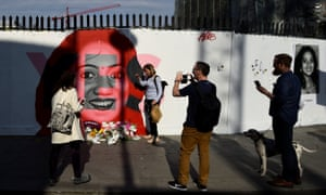 People gather around as flowers are left at the foot of a new mural of Savita Halappanavar.
