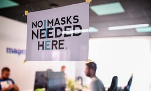 A sign reading 'No Masks Needed Here' displayed at a graphic design studio in the town of Gjilan.
