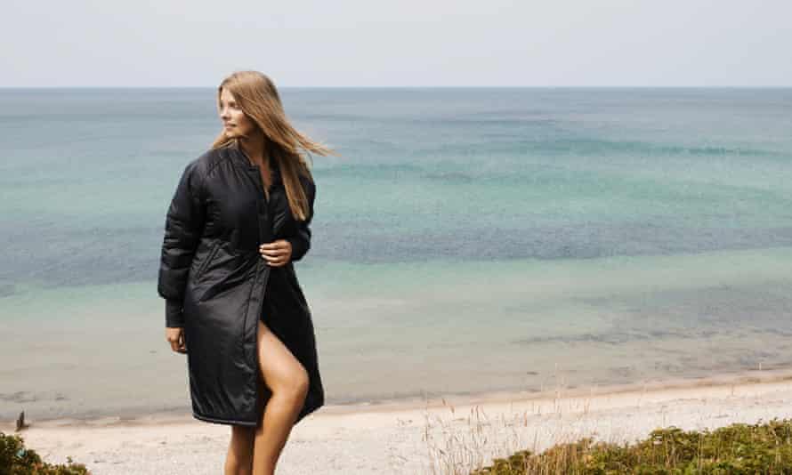 A model wears a Moshi Moshi Mind coat on a beach