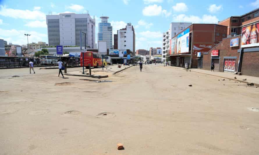 A handful of pedestrians walk the streets of Harare following President Emmerson Mnangagwa's declaration of a national lockdown