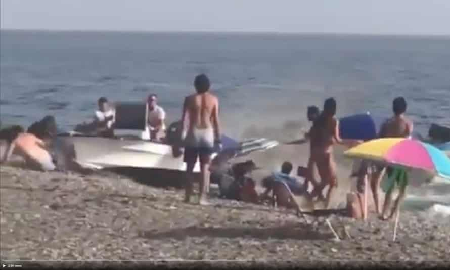 Bathers react after a boat is run aground.