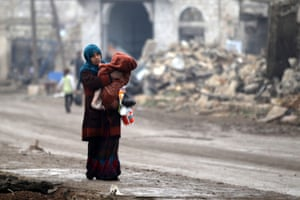 A woman carries a child as she walks near rubble of damaged buildings in al-Rai town, northern Aleppo.