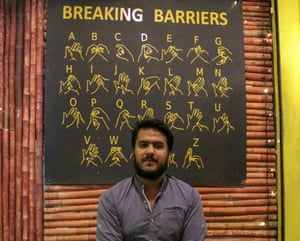 Owner Sheikh Faizan Raza in front of a board with signs for the alphabet at the cafe.