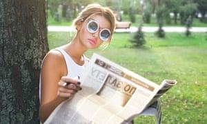 Woman sitting under tree, reading newspaper