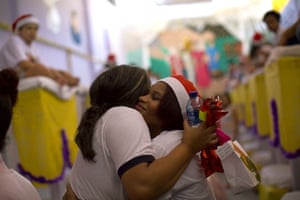 An inmate wearing a Santa hat hugs a volunteer