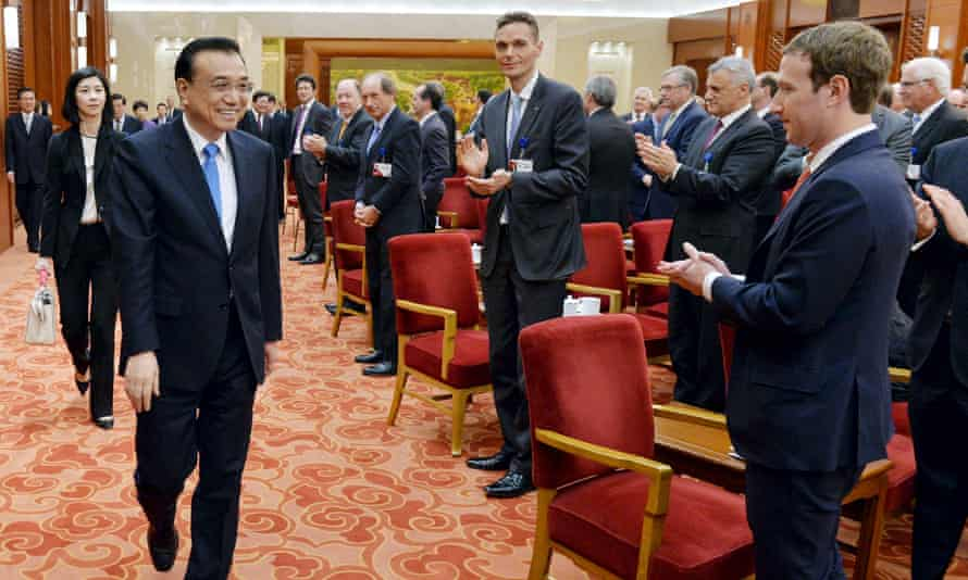Facebook's CEO Mark Zuckerberg and the overseas representatives of China Development Forum applaud for the arrival of Chinese Premier Li Keqiang at a meeting at Great Hall of the People in Beijing in March