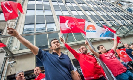 Erdoğan supporters hold Turkish flags in front of the Turkish embassy in Brussels.