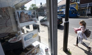 A woman walking past an estate agent's window without looking in