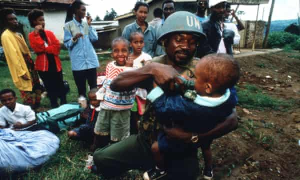 A UN soldier bottle-feeds a child in Rwanda, 25 May 1994.