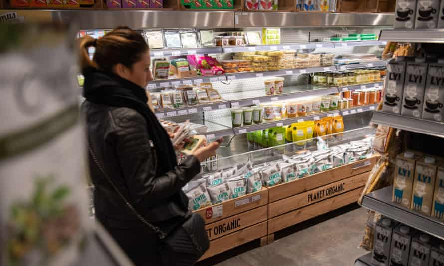 A shopper browses vegan produce at a supermarket.