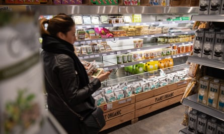 A shopper browses vegan produce at a supermarket.