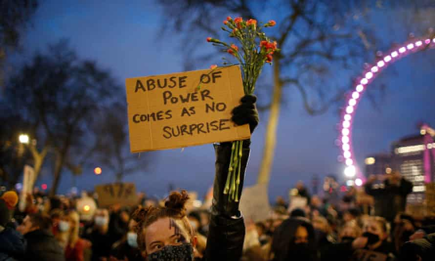 A woman holds a banner during a protest against violence against women and new proposed police powers.