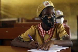 Students from Opebi junior grammar school, wearing face masks to protect against coronavirus, attend lessons in Lagos.
