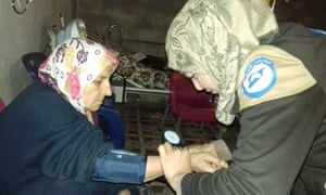 A volunteer offers medical help at a women's centre in Idlib, Syria.