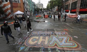 People walk past street art that reads 'Welcome to Chaz' inside what is being called the 'Capitol Hill Autonomous Zone' in Seattle.