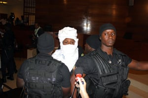 Security guards surround the former Chadian dictator Hissène Habré on his first appearance at the special international court in Senegal's capital Dakar.