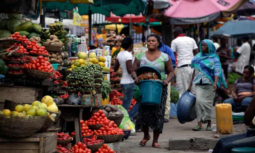 Women sell vegetables in a market in Lagos, Nigeria
