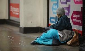 A homeless woman sits near Trafalgar Square, London
