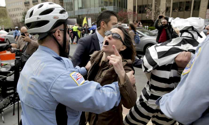 A Metropolitan police officer separates a protester from a member of the Turkish security detail in front of the Brookings Institute in Washington DC, 31 March.