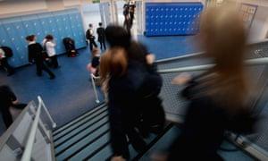 Pupils walk down a secondary school corridor.