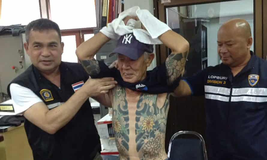 Shigeharu Shirai, a retired Japanese crime boss, is paraded by Thai police to show his gang-style tattoos.