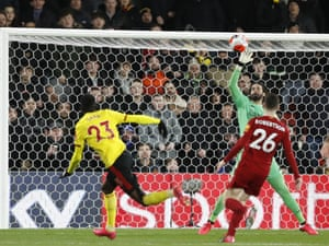Liverpool's goalkeeper Alisson makes a save in front of Watford's Ismaila Sarr.