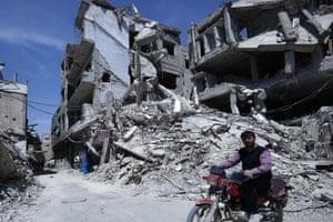 A man rides past a scene of destruction