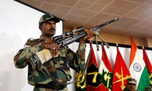An Indian soldier displays a US-made sniper rifle recovered along with a Pakistani-made mine after searches in the region