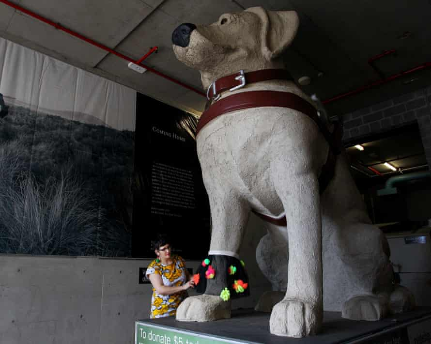 Nicole Barakat, Artist Educator at the MCA puts a textural ruffle around the paw of Gulliver, a giant guide dog statue.