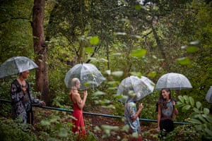 Models wait under umbrellas backstage at the Koche womenswear spring/summer 2021 show in the Jardin des Buttes Chaumont.