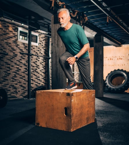 A man stepping onto a wooden box at the gym.