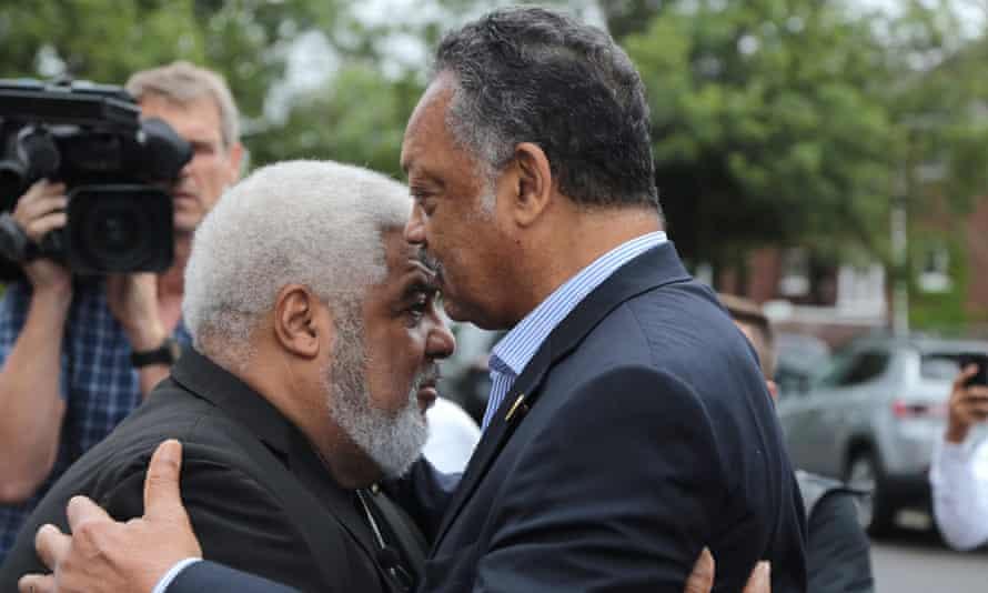 The Rev Jesse Jackson and the Rev Robert Smith Jr speak outside New Bethel Baptist church on 16 August.