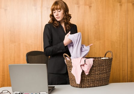 Woman dressed in suit, folding laundry into a basket, looking down at laptop