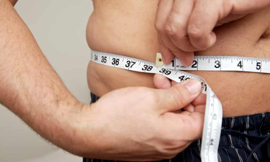 Close-up of a man measuring waist with tape measure.