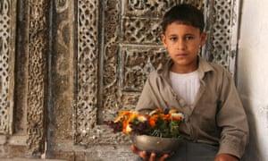 Yemen. Jibla Mosque. Boy and flowers